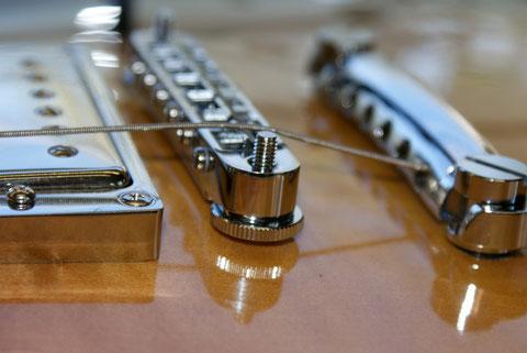 Nach dem Anpassen des Sattels, kann die Saitenhöhe eingestellt und die Schrauben gekürzt werden.