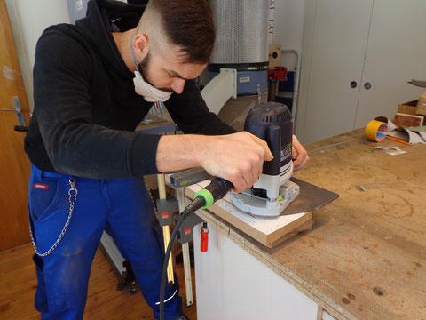 Mit einer extra angefertigten Schablone kann in das abgeschrägte Korpusteil gefräst werden.