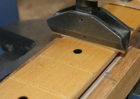 Nach der Überarbeitung und Vorbereitung werden die Edelstahlbünde vorgebogen und in die Bundschlitze gepresst.