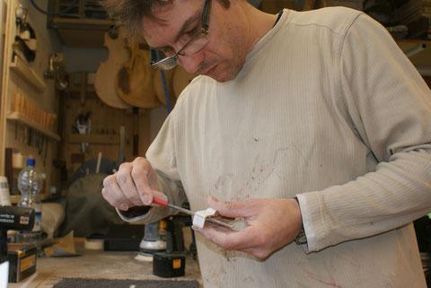 Auch die Kappen für die Tonabnehmer müssen vorbereitet werden. Mit einer Rundfeile bearbeite ich die Löcher für die Stabmagnete. Wenn da zu viel Lack stehen bleibt, passen sie später nicht mehr.