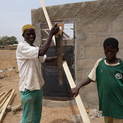 Schreiner mit Sohn beim Bau des Daches für die Toiletten