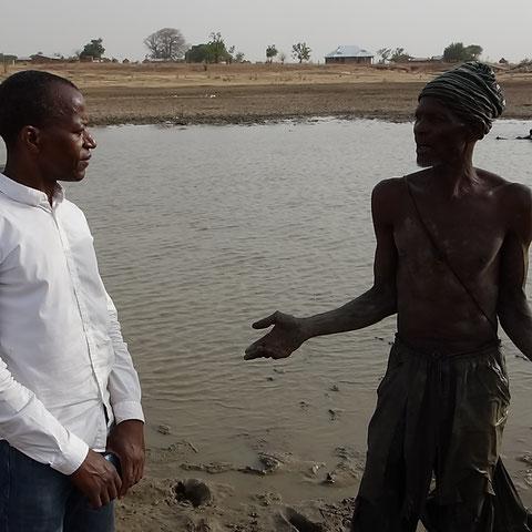 Ibrahim unterhält sich mit einem Fischer, es gibt kaum noch Fische