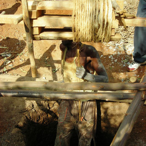 uomo che si cala nel pozzo per continuare lo scavo