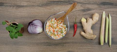 Oregano, Zwiebeln, Chili, Ingwer, Zitronengras und Taste of Asia Salz in einer Reihe auf einem Holzhintergrund