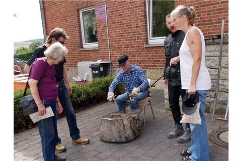 Die Besucher schauen Andreas Held zu, der eine Sense dengelt.