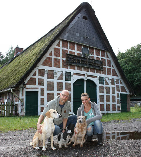 Matthias und Isabelle Krämer mit ihren Hunden Nala, Buddy und Jolly. Im Hintergrund ist das Haus zu sehen, das das Paar gepachtet hat - ein ehemaliges Försterei-Gebäude. Foto: van Veenendaal