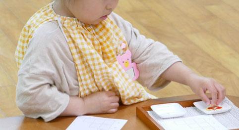 幼児教室フィオーレコース(2歳児)のモンテッソーリ活動で、生徒が集中して、シールを貼る活動を行っています。