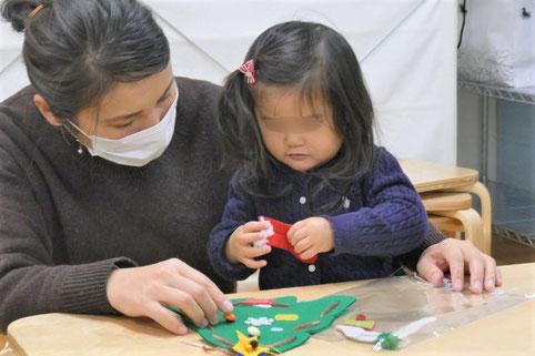 1歳児クラスの生徒が、お母さまといっしょにクリスマスの製作をしています。