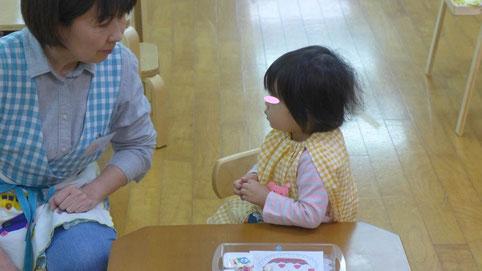 幼児教室フィオーレコース(2歳児)のモンテッソーリ活動で、果物のシールをケーキの絵に貼って、ケーキを完成させる活動に取り組む生徒を先生が援助しています。
