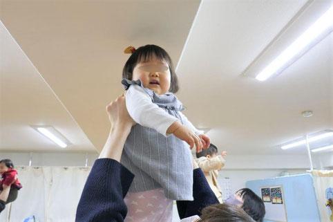 幼児教室の1歳児コースのリトミックで、ピアノに合わせて、高く持ち上げられ、盛り上がっています。