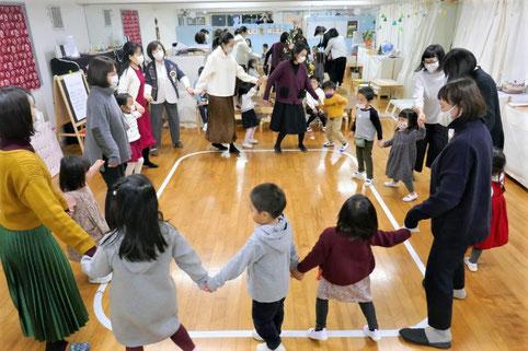 幼稚園児クラスのリトミックでクリスマスソングに合わせてダンス、輪をつくって協調して動いています。