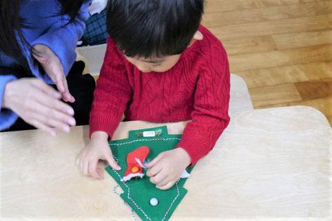 幼児教室の2歳児クラスの生徒がお母さまにサポートいただきながら、クリスマスの製作を行っています。