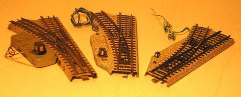 Vergleich der Elektroweichen von links nach rechts: Nachkriegsstandardgleis Weiche 3600, frühe M-Gleis-Weiche mit großer Laterne und spätere Ausführung mit kleiner Laterne.