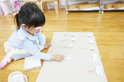幼児教室の幼稚園児クラスで、生徒がモンテッソーリ活動の中の数の活動に集中しています。