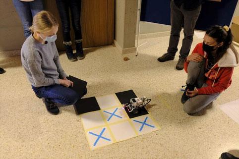 Schülerinnen spielen Tic Tac Toe mit oder gegen einen Roboter.