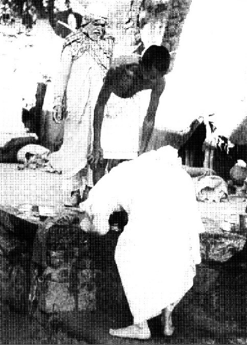 7th November 1954 : Meher Baba at the leper colony in Pandharpur, bowing to the leper after washing him, with Saint Gadge Maharaj looking on.