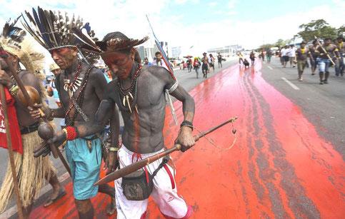 """Fra en protestaktion af indigene folk , april 2018 : """" I det vi farver gaderne røde, viser vi, hvor meget blod der er blevet udgydt i kampen for at beskytte vores områder""""."""