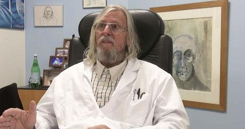 D. Raoult 2019, avec toute sa panoplie : cheveux longs, barbe, moustache et BLOUSE