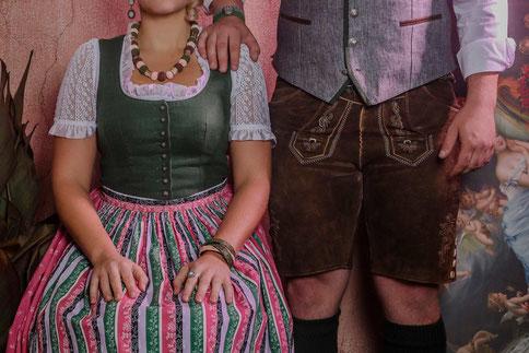 Junge Frau im Dirndl sitzt, junger Mann in Lederhose steht daneben, sie trägt Trachtenschmuck