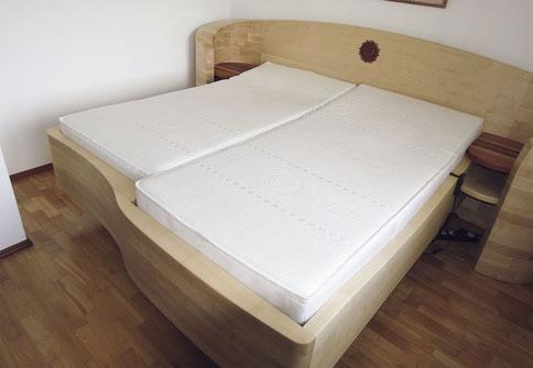 """Bett """"Passgeneu"""" aus massivem Ahorn mit einseitig verkürzter Liegefläche, gebogenes Kopfteil mit Sonne und integrierten Ablagen"""