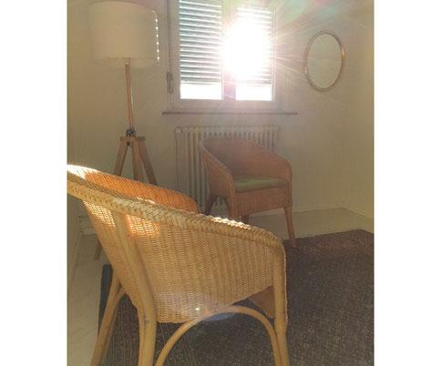 Auf dem Bild ist der Praxisraum von Sandra Lehner zu sehen. Man sieht die Sonne, die zum Fenster hereinleuchtet. Rechts neben dem Fenster hängt ein ovaler Spiegel mit Goldrahmen. Links neben dem Fenster steht eine Lampe. Davor stehen zwei Ratanstühle.
