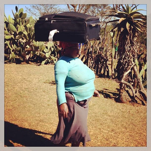 Mamage trägt unsere Koffer zum Auto