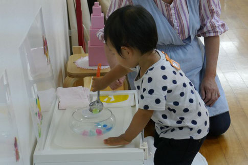 モンテッソーリの活動で、1歳児が金魚すくいの活動を何回も繰り返して行っています。
