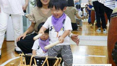 教室の夏祭りで和太鼓体験。1歳児が両手にばちを持って、とても楽しそうに締太鼓をたたいています。