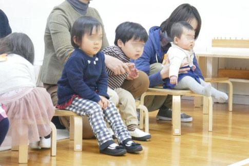 リトミックで先生のお話を、0歳、1歳児、2歳児が集中して聞いています。幼児前期に説く貯油的な吸収精神がよく現れています。