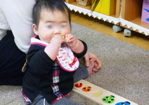 モンテッソーリの活動で、0歳児が口を使って教具を確かめています。