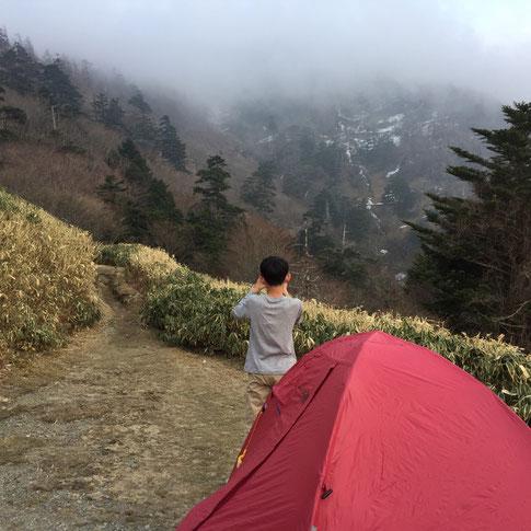 なんだかんだで16時に無事にテント場到着♪ *わかりにくいけどトラバースが確認できる写真があったんで、、奥に観えている剣山の中腹、、ガスの下に白い雪の横線。 ここです。 画像だと少ししか見えてませんけど実際は残雪がイラストのように谷間に傾いて残り、幅15㎝くらの縁を歩く感じ! 長くて100m、短い所で5mくらいの残雪が不規則な破線のように1.6km続いています!
