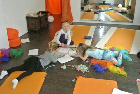 Zum Ende der Kinderyoga Stunde malen und basteln drei Kinder