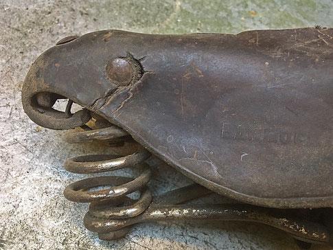 Verhärtung und Risse im Leder an einer seitlichen Niete der Sattelnase bei einem historischen Fahrradsattel mit Lederdecke