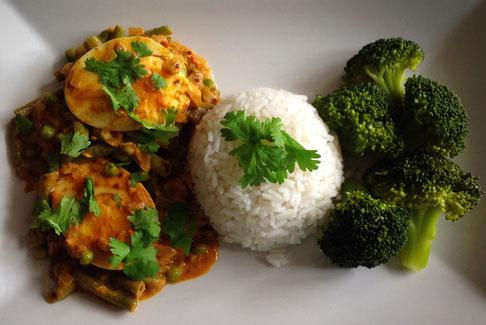 Vegetarische curry met eieren, witte rijst en gestoomde broccoli.
