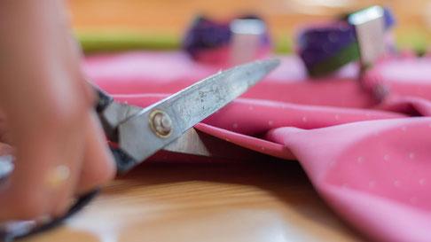 Eine Hand schneidet mit der Schere pink gemusterten Trachtenstoff
