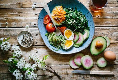 Eine bunte Bowl mit Tomaten, Eiern, Zucchini,, Avocado und Grünkohl