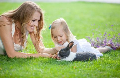 Jeune femme et sa fille jouant avec un lapin dans un parc