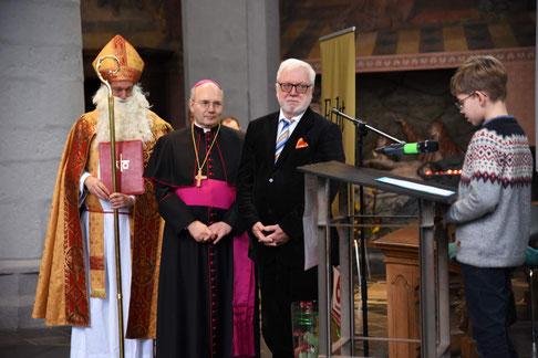 Ein Schüler trägt Bischof Nikolaus, Bischof Dieser und Bürgermeister Norbert Plum (v.l.) seine Forderungen gegen Kinderarbeit vor. © Theresa Meier
