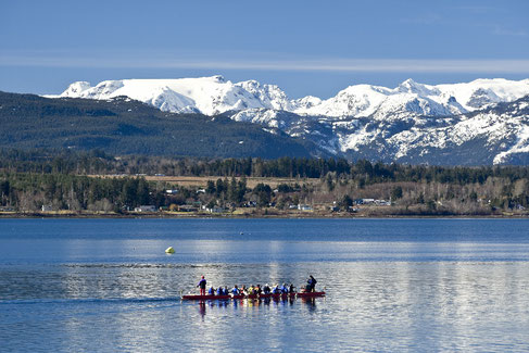 A dragon boat paddling on the Comox bay with the glacier in the background.