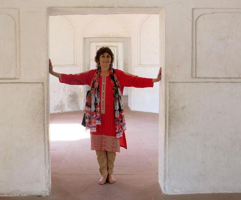 Rehana Webster barfuß und mit ausgestreckten Armen in einem Tor in Pakistan