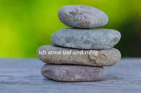 vier Steine übereinander gestapelt auf untergrund mit grünem Hintergrund