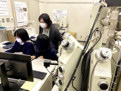 当研究室の学生の分析を指導しているところです。コロナ禍で、研究室でも全員常時マスクを着用しています。電子線マイクロプローブアナライザーという装置を使って鉱物の化学的特徴を明らかにしています。