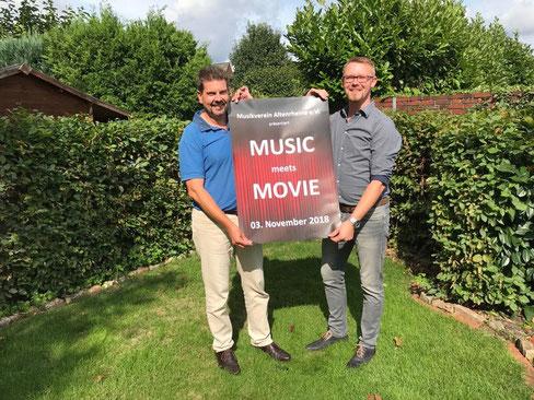 """Vereinsvorsitzender Klaus Volkmer (l.) und Michael Kleene, zweiter Vorsitzender, präsentieren das Plakat zum Jahreskonzert """"Music meets Movie""""."""