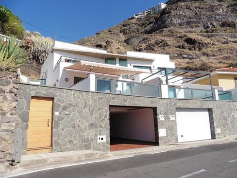 Blick von der Strasse auf das Haus. Im unteren Teil sieht man die Garage und darüber befindet sich eine große Terrasse und dann kommt das Haus mit Berge im Hintergrund.