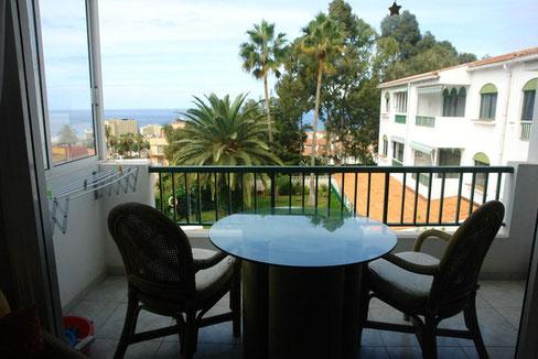 Balkon mit Gartenmöbeln und Blick über den Gemeinschaftsgarten bis zum Meer von Teneriffa.