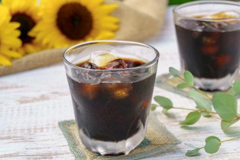 積み重ねられた本。広げられたノートとボールペン、眼鏡。コーヒーの入ったマグカップ。アイビーの葉。