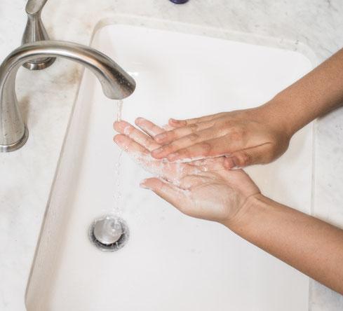 Zwei Hände unter einem Wasserhahn, um sich zu waschen.