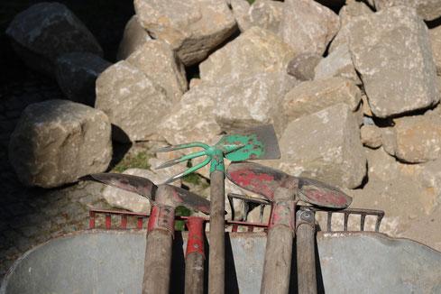 Schubkarre mit Werkzeug und Natursteinen im Hintergrund