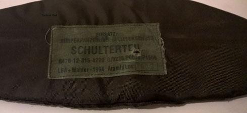 Schulterteil einer Splitterschutzweste von 1994 mit Einschussloch. Das 9mm Para Geschoss wurde gehalten.