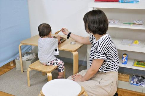 幼児教室のモンテッソーリ活動で1歳児のお子様の活動を、お母さまが見守りながら観察しています。